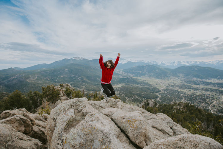 Girl jumping with arms raised on mountain against sky