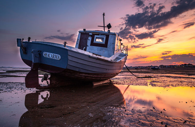 Ship moored at beach against sky during sunset