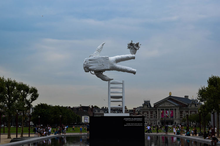 View of sculpture in city against cloudy sky
