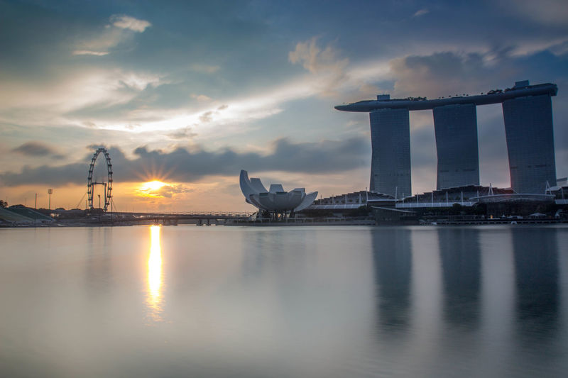 Artscience Museum With Marina Bay Sands Reflecting In Water Against Sky During Sunset