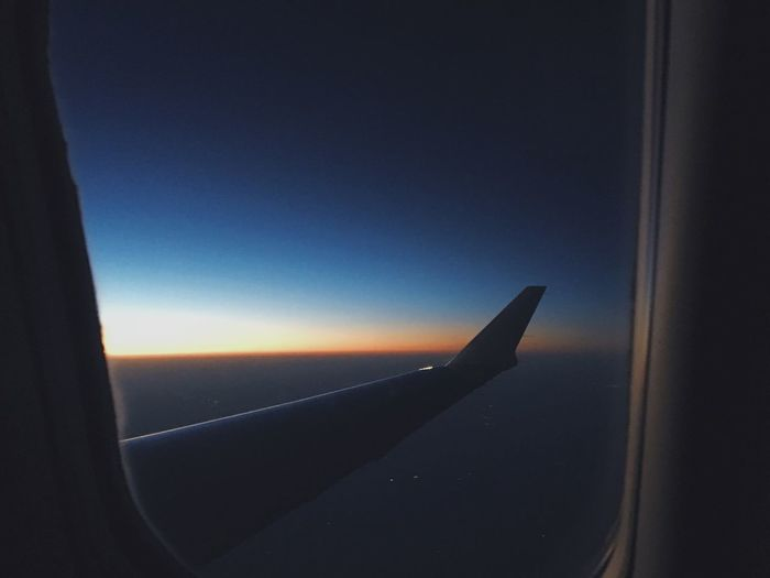Airplane wing against clear blue sky seen through window
