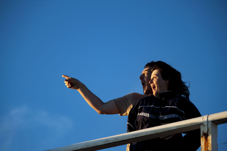 Man pointing with woman against blue sky