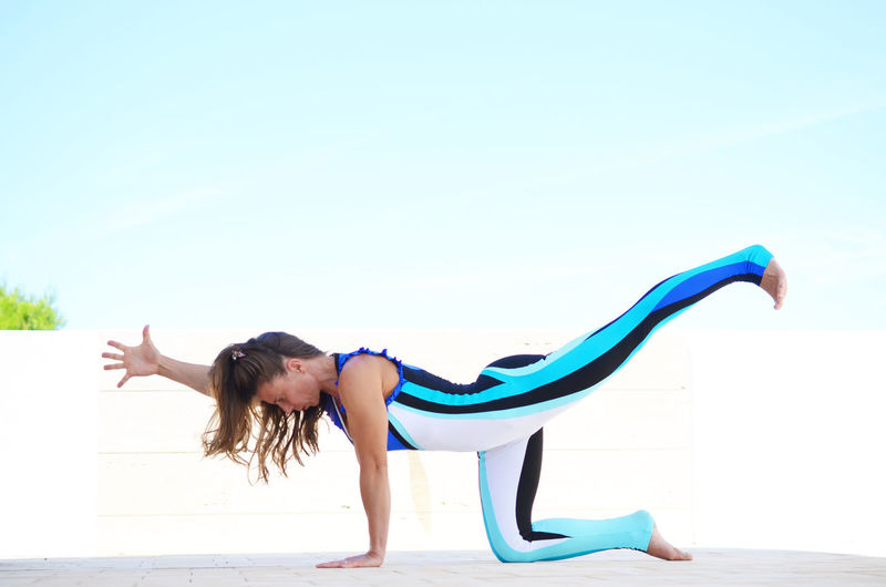 Side View Of Young Woman Practicing Yoga On Terrace Against Clear Blue Sky