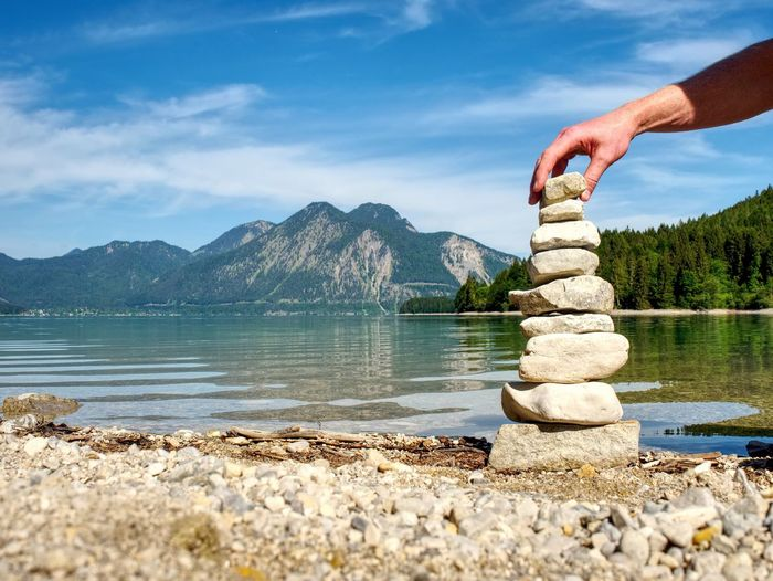 Human hand on rock by lake against sky