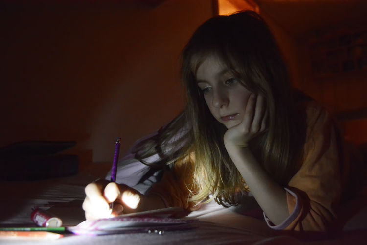 Close-up of girl writing in paper on table at home