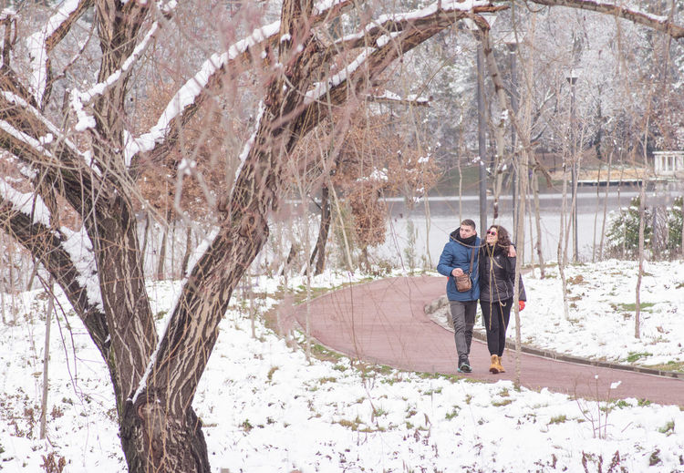 Man and woman walking on snow covered tree