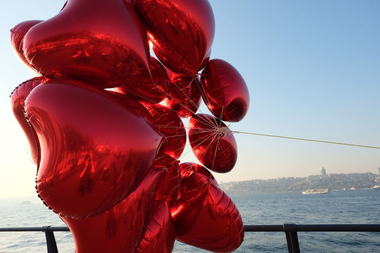 Close-up of red balloon against sea