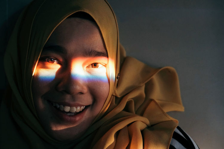 Close-up portrait of spectrum on girl face against gray background