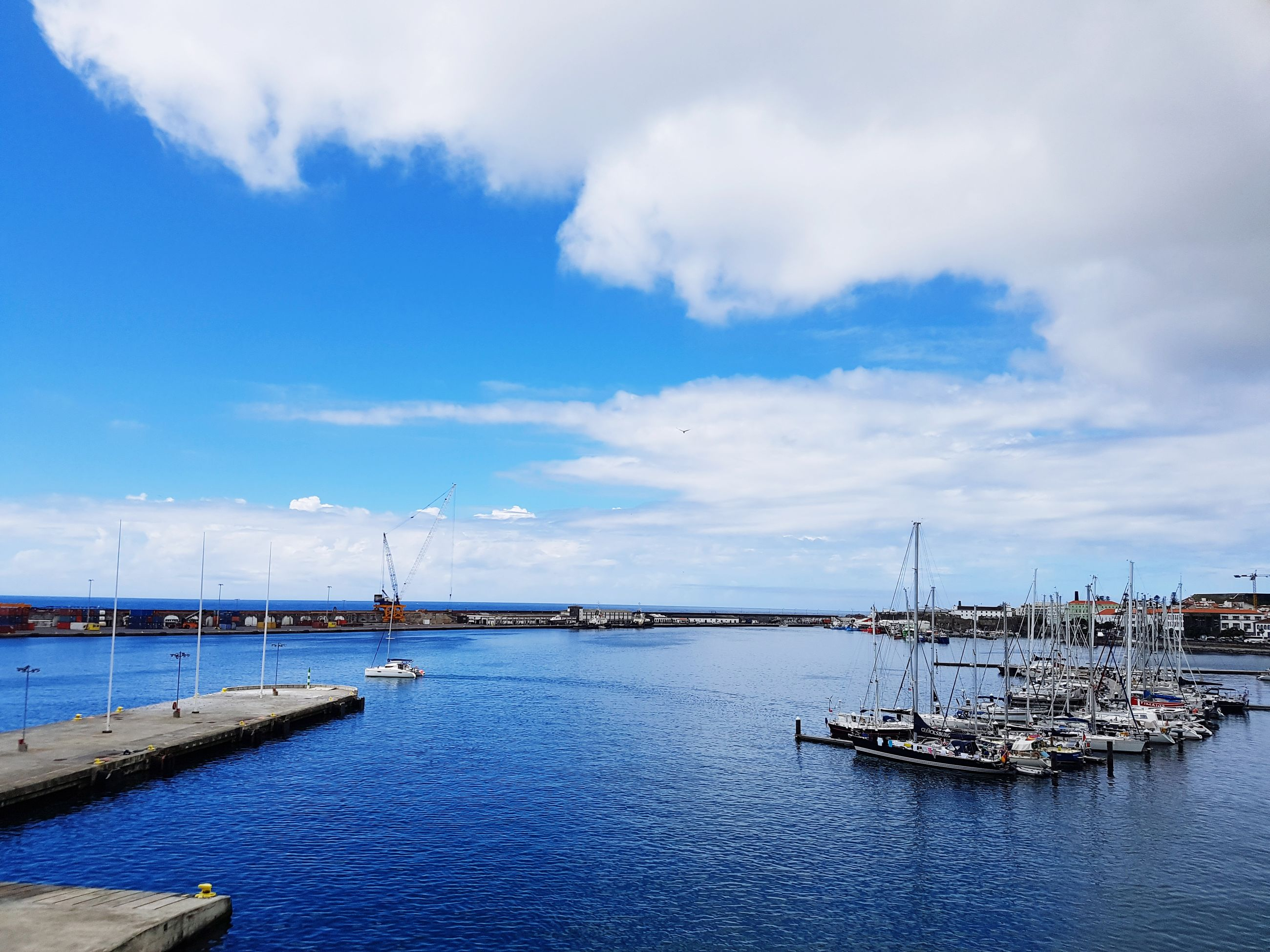 cloud - sky, water, sky, transportation, nautical vessel, no people, sea, outdoors, day, nature, mode of transport, bridge - man made structure, blue, architecture, harbor, built structure, travel destinations, scenics, beauty in nature, mast, wind power, wind turbine, windmill