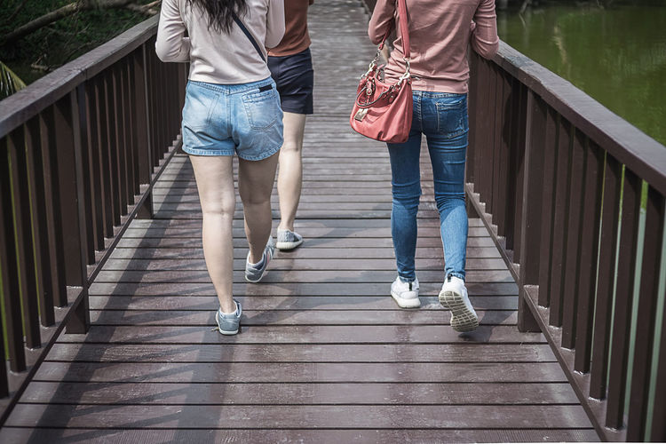 Low section of friends walking on footbridge