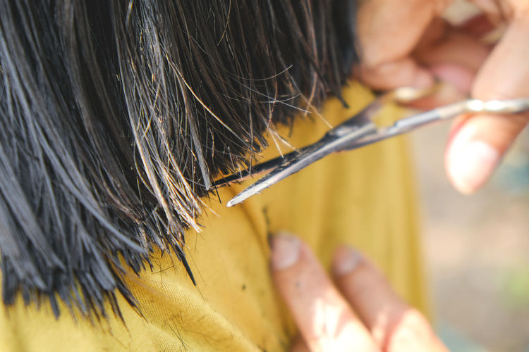 Cropped hands cutting customer hair