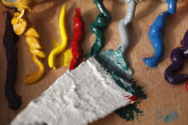 High angle view of colorful paints on table at workshop