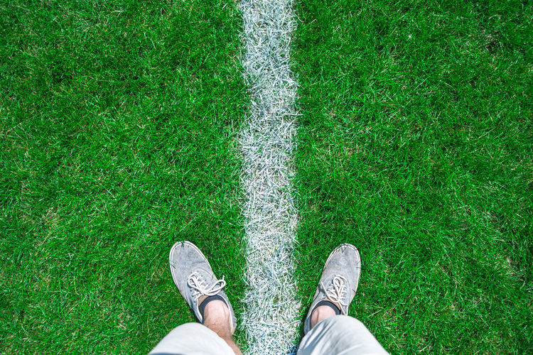 First person view of human feet on grass with dividing line Adult Canvas Shoe Day Directly Above Dividing Line Field Football Grass Green Color High Angle View Human Body Part Human Leg Lifestyles LINE Low Section Men Nature One Person Outdoors People Personal Perspective Real People Shoe Sports Standing