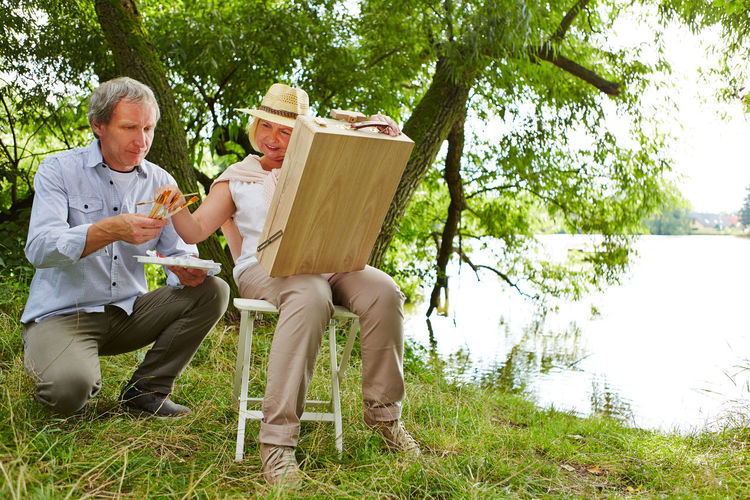 Full length of senior woman painting while sitting by lake with husband