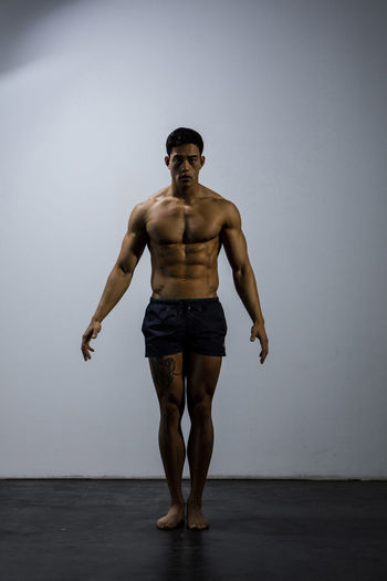 Portrait Of Shirtless Muscular Man Exercising Against Wall