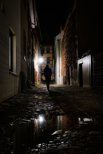 Rear view of man walking on illuminated street amidst buildings at night