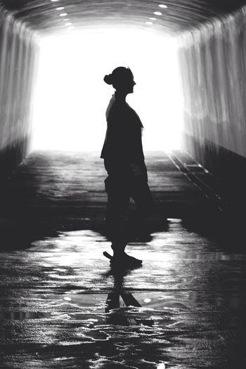 Side View Of Silhouette Woman Standing On Wet Road In Tunnel