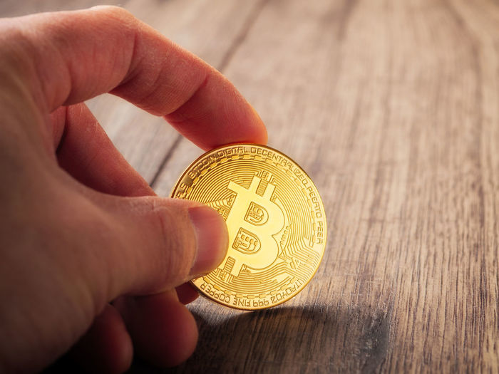 Cropped hand of person holding bitcoin on table
