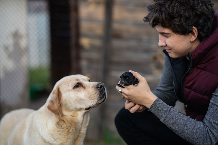 Side view of man with dog. young man holding a little puppy of labrador in his hands