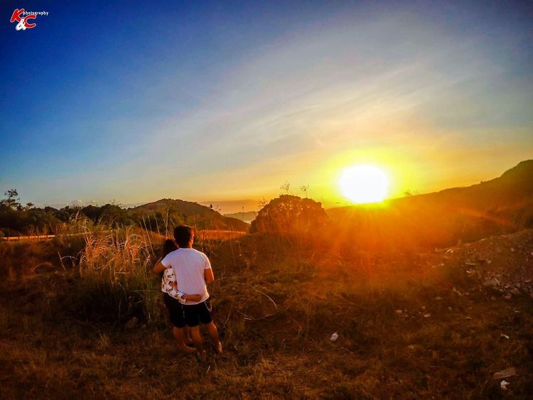 Togetherness Rear View Sunset Full Length Sky Sun Nature One Person Real People Lens Flare Sunlight Outdoors Leisure Activity Beauty In Nature Scenics Field Childhood Tranquility Tree Tranquil Scene Sunbeam