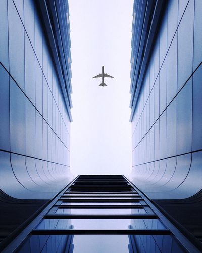 Low Angle View Of Modern Building Against Airplane Flying In Clear Sky