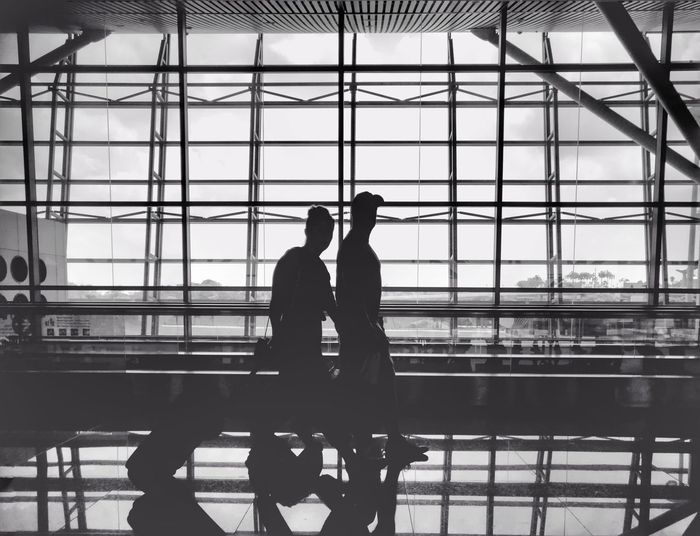 traveling Love Reflection Flight Friendship Relationship City Men Bridge - Man Made Structure Hardhat  Sky Architecture Built Structure Airport Departure Area Airport Terminal Public Transportation Moving Walkway  Airport Check-in Counter Transportation Building - Type Of Building Arrival Departure Board Single Parent