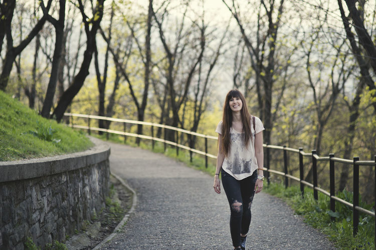 beautiful young woman walking outside in the girl with long brown hair smiling Bare Tree Beautiful Woman Casual Clothing Clothing Day Footpath Front View Full Length Hairstyle Leisure Activity Lifestyles Nature One Person Outdoors Plant Portrait Railing Real People Tree Young Adult Young Women