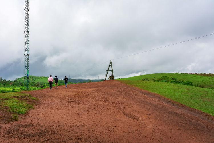 People walking on field against sky
