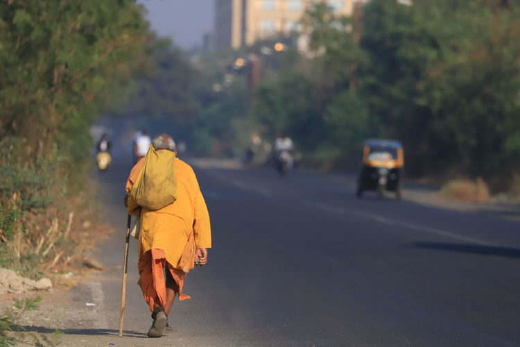 Rear view of man in traditional clothing walking on road