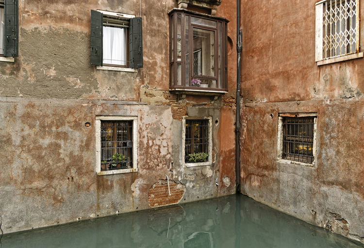 A hidden corner of old traditional Venetian buildings with red bricks and concrete on a canal in Venice, Italy. Typical Italian architecture Antique City Orange Reflection Romantic Rugged Textured  Venetian Wall Architecture Bricks Building Canal Cement Concrete Corner Facade Building Hidden House Italy Old Traditional Venice Water Window