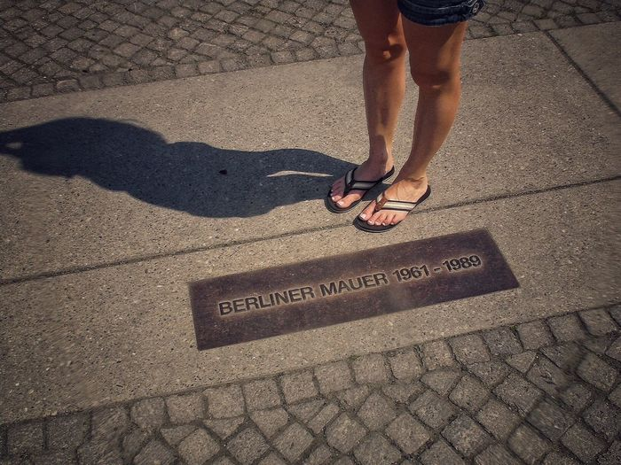 Low Section Of Woman Standing On Cobblestone