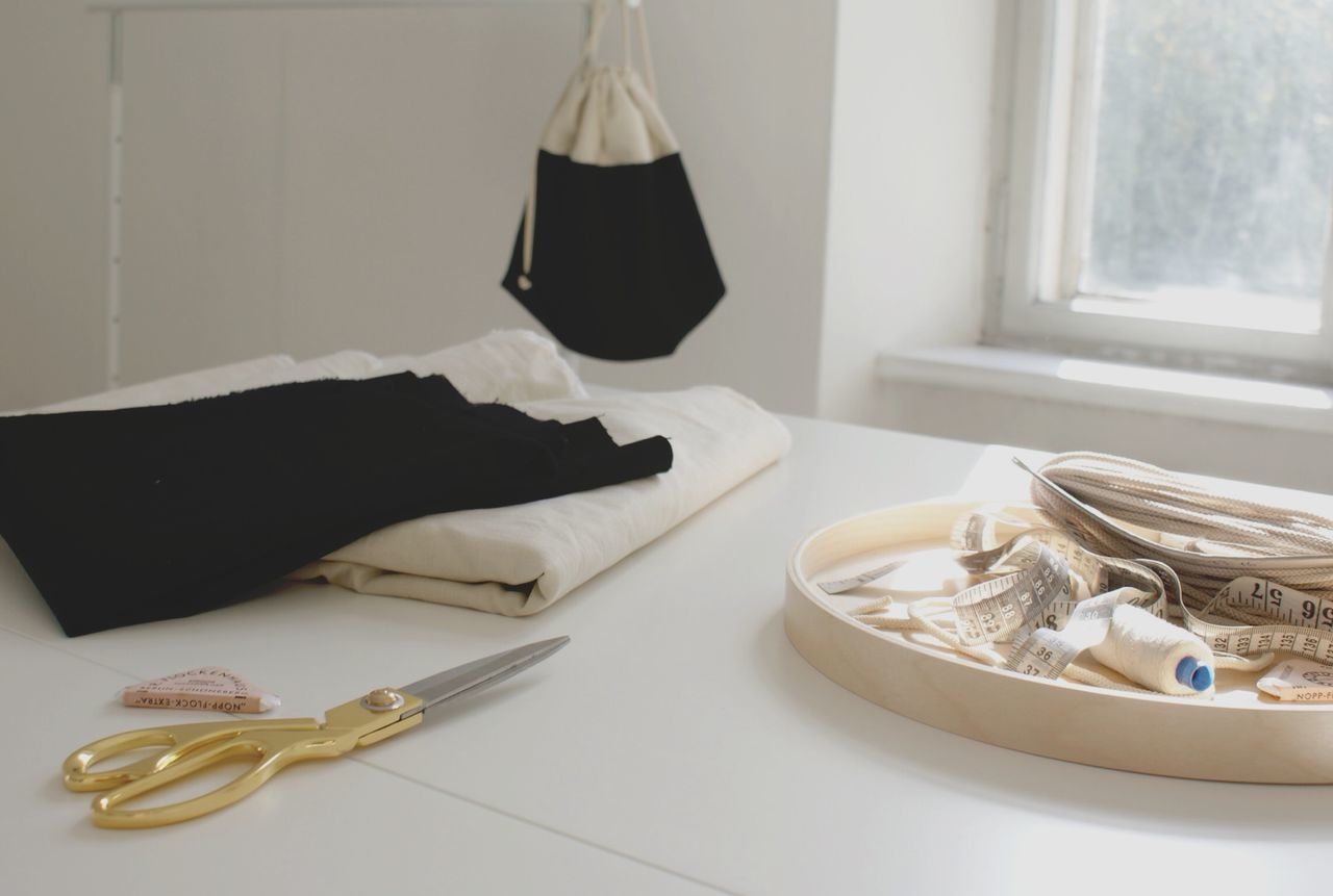 High angle view of sewing items on table against window