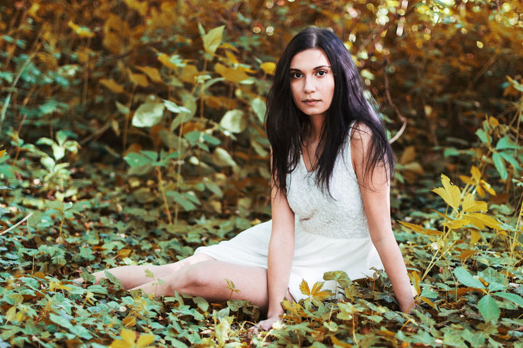 Portrait of beautiful young woman sitting in forest during autumn
