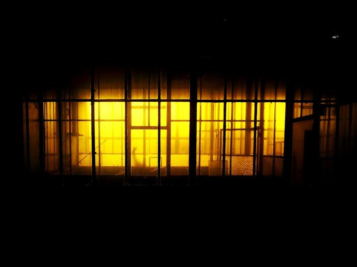 Illuminated building seen through window at night