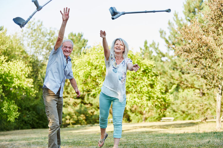 Happy couple throwing crutches in park