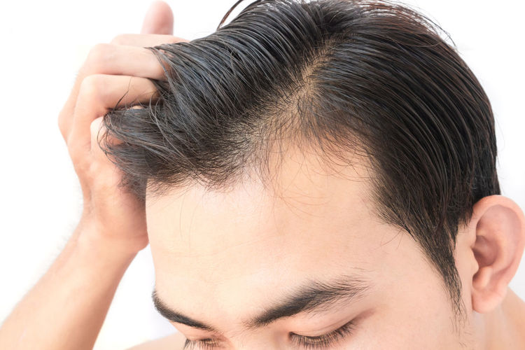 Cropped image of man with hand in hair against white background