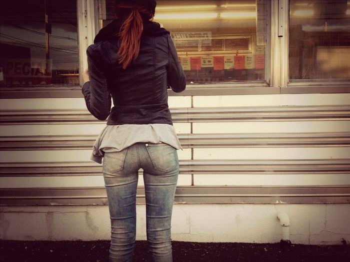Rear view of a woman standing in the dark