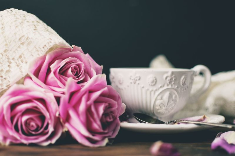 Close-Up Of Rose Bouquet And Coffee Cup On Table