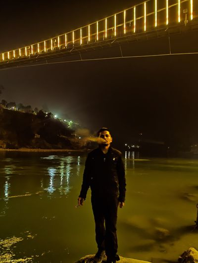 Full length of man smoking cigarette standing by river against sky at night