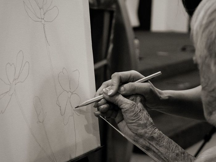A volunteer teaching an elder to paint a picture of her choice. Indoors  Human Hand Elders Kindness Compassion