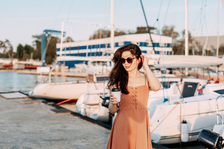 Portrait of young woman in sunglasses standing on boat