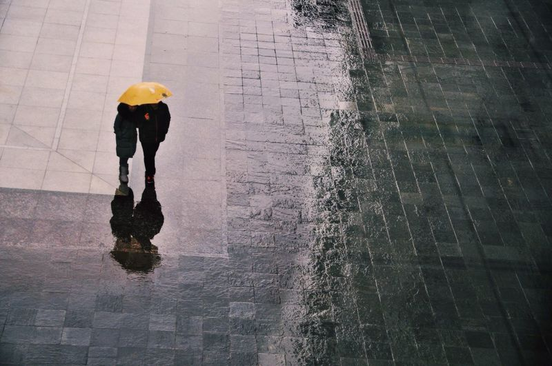 High angle view of friends with umbrella while walking on wet street during monsoon