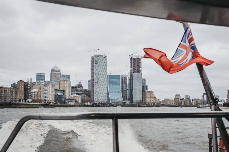 View of Canary Wharf skyscrapers from Thames Clippers boat on River Thames, British Naval Flag on the mast. Canary Wharf is a busy financial area of London, UK. Sightseeing Tourist Attraction  Tourism Modern Modern Architecture Horizon View Ship River Boat Travel Destinations Architecture Patriotism Sky Flag Cloud - Sky Building Exterior Day Water City No People Wind Cityscape Outdoors Naval Flag Union Jack River Thames Canary Wharf Uk London Built Structure Building Nature Office Building Exterior Skyscraper Tower Tall - High Independence