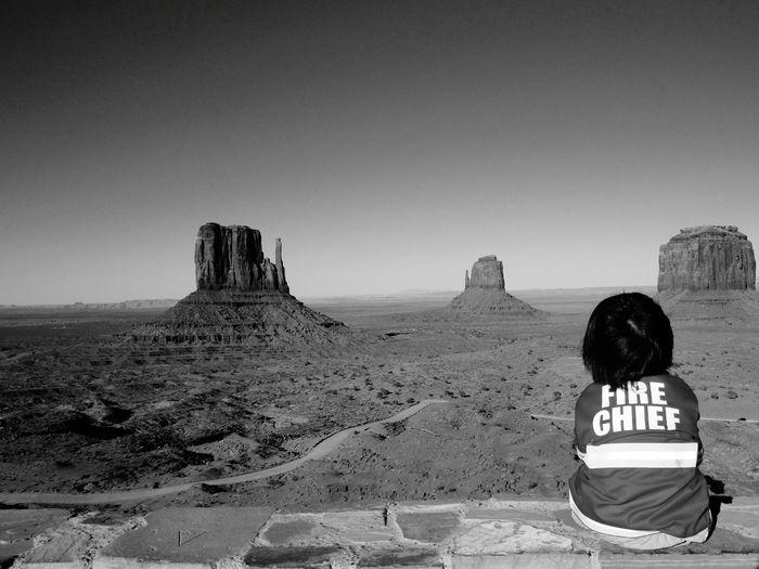 Rear View Of Child Sitting Against Desert