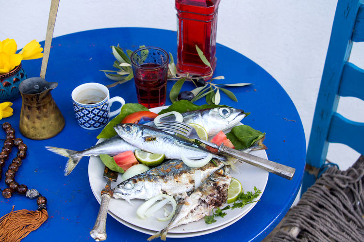 a plate of fresh and grilled fish, red wine and a cup of Mocha Mocha Red Wine Animal Blue Briki Coffee Cup Container Crustacean Fish Fishing Industry Flowers Food Food And Drink Freshness Greek Chair Healthy Eating High Angle View Komboloi No People Plate Ready-to-eat Seafood Table Vertebrate Wellbeing