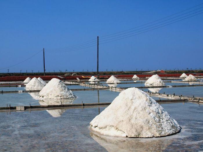 Salt heap against clear blue sky