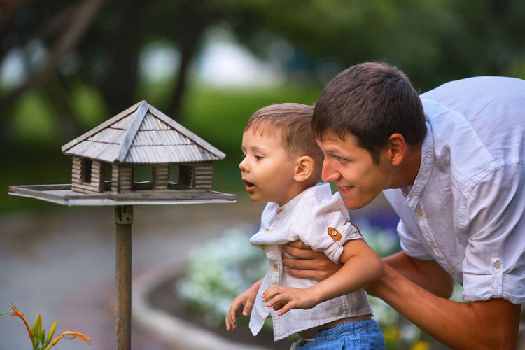 Dad and his son on a walk in the summer in the park. father and child look into the bird feeder.