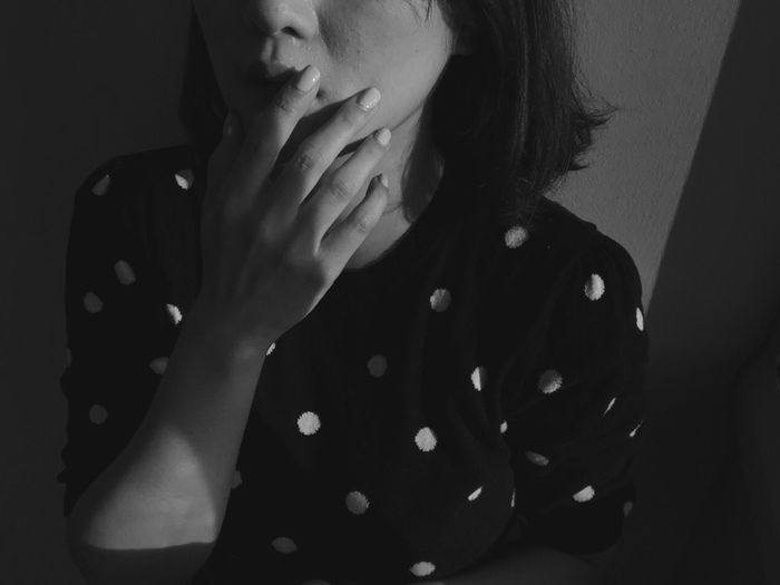 Midsection Of Woman With Fingers On Lips