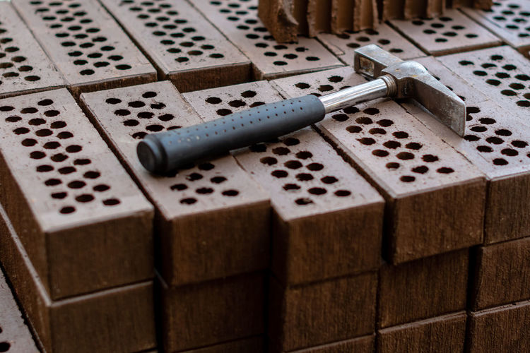 A hammer is laid on a red brick stack. Architecture Construction Decor Exterior Red Wall Arts Culture And Entertainment Backdrop Background Block Box Box - Container Brick Brickwork  Building Cement Choice Close-up Concrete Container Design Flooring Group Group Of Objects Hammer High Angle View Indoors  Large Group Of Objects Leisure Games Mason No People Pattern Relaxation Selective Focus Still Life Stone Surface Table Texture Tools Tray Wood - Material