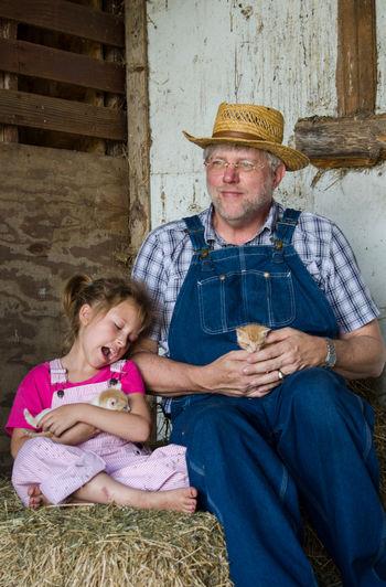 grandpa shares new born kittens with his little granddaughter Farmer Kittens Visiting Grandpa Adult Bonding Family Farm Feline Hat Little Girl Men New Kittens Overalls People Pink Color Senior Male Sharing  Sitting Togetherness